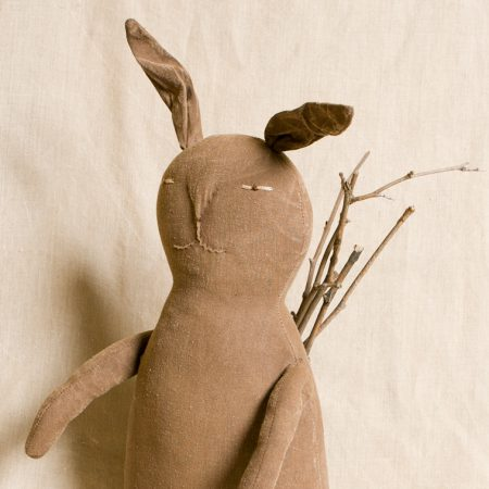 Front view of large rabbit doll with backpack and sticks designed by Tish Bachleda